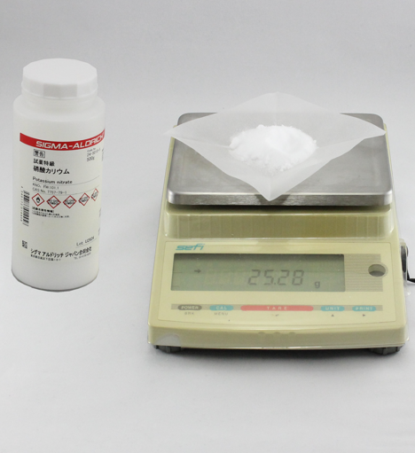 Fig. 2 Weigh the potassium nitrate (1) using folded and creased weighing paper (2) with an electronic balance.